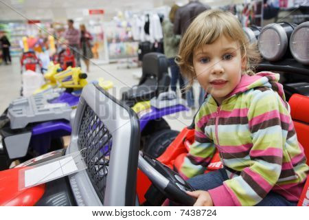 little girl in supermarket alone chooses in department of toys