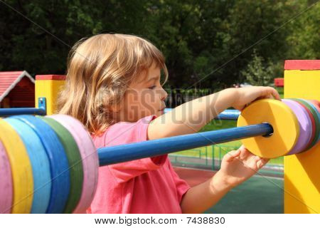 girl playing at playground in summer sunny day moves colour rings