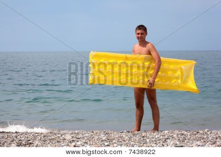 young guy with yellow mattress on seacoast.