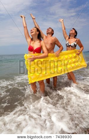trio of young people have fun on seacoast and hold yellow inflatable mattress