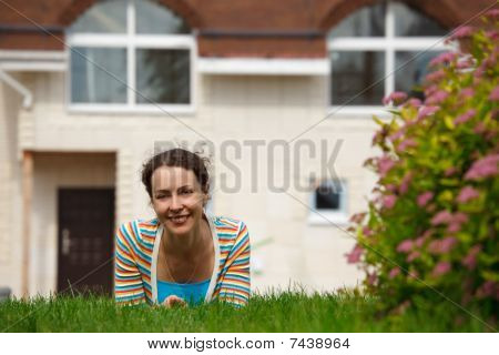 Happy girl on lawn in front of new home. Smiling she looks into camera.