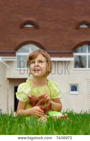 little girl sitting on lawn in front of new home.