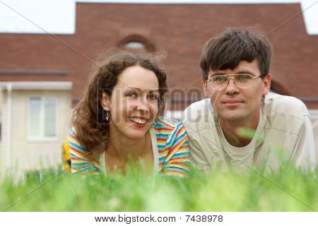 Guy with girl lying on lawn in front of new home.