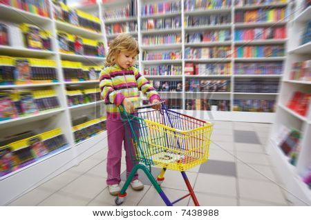 Little girl in bookshop with cart for purchases.