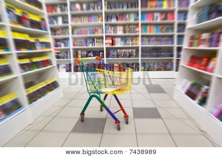 Bookshop interior. Before racks with books there is bright cart for purchases