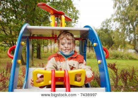 In autumn afternoon boy plays children's playground.