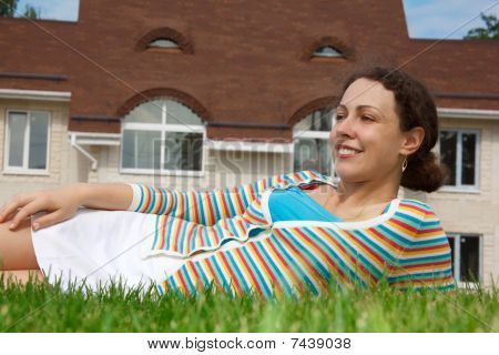 Happy girl on lawn in front of new home.