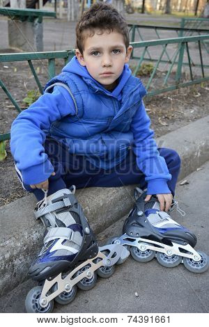 Sad Little Boy Sits Shod Rollers On The Curb.