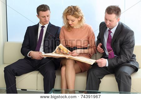 Businessmen and a woman reading a newspaper sitting on a white couch