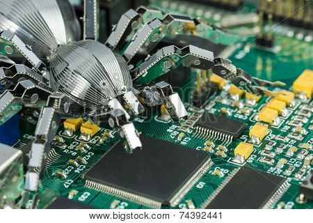A metal spider standing on a printed circuit board