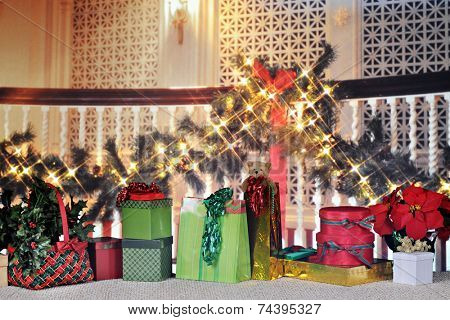 Multiple Christmas decorations and gifts along a garland and light decked interior banister.
