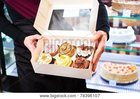 Woman presenting muffins and cupcakes in takeaway boxes in cafe or pastry shop