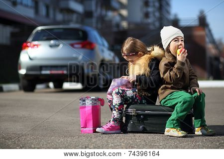Young children sitting on a suitcase on the road: girl opening her purse, boy eating an apple