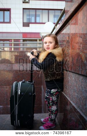 Pretty little girl stands with a large green suitcase near wall