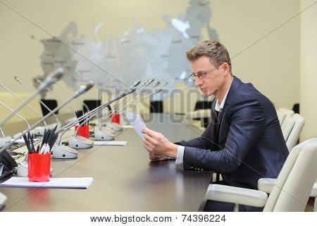 Young businessman in glasses sitting at negotiating table and reading the document