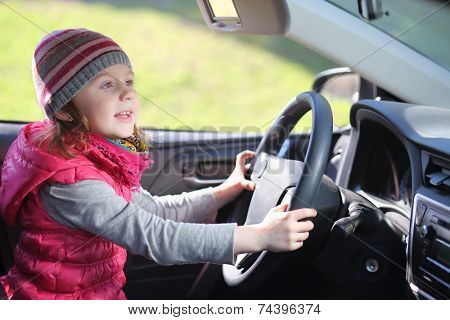 Happy little girl in pink waistcoat and striped hat sitting at wheel of car