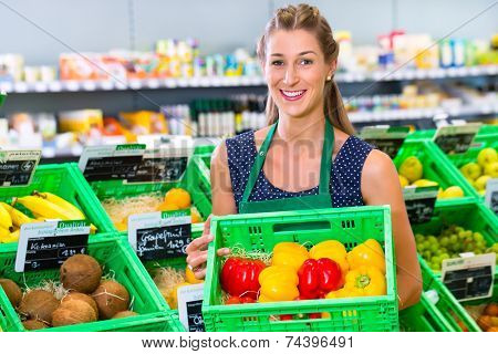 Female organic grocery shop assistant filling up coconuts storage racks in vegetable department