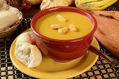 stock photo of butternut  - a bowl of butternut squash soup with dinner rolls - JPG