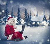 picture of social housing  - Santa Claus surfs on internet with a laptop - JPG