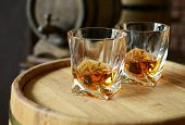 stock photo of tumbler  - Glasses of brandy in cellar with old barrels  - JPG