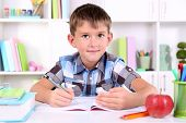 pic of schoolboys  - Schoolboy sitting at table in classroom - JPG