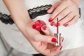 Woman Applying Red Nail Polish poster