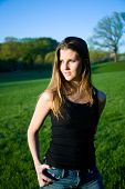 picture of wife-beater  - young woman standing in park wearing jeans and a black wife beater - JPG