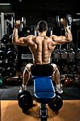 stock photo of arm muscle  - very brawny guy bodybuilder execute exercise with dumbbells on deltoid muscle shoulder - JPG