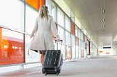 pic of carry-on luggage  - Full length rear view of young businesswoman with luggage rushing in railroad station - JPG