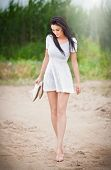 foto of legs air  - Attractive brunette girl with short white dress strolling barefoot on the countryside road. Young beautiful woman walking with shoes in hand with forest in background. Female with long legs outdoor