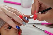 stock photo of finger-painting  - Finger nail treatment painting lines with brush and lacquer - JPG