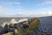 image of dike  - Basalt stones along a dike in a stormy sea - JPG