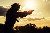 stock photo of pistols  - Silhouette of police officer with pistol at sunset - JPG