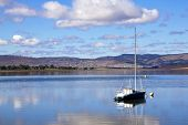 image of natal  - Landscape view of yacht in Midmar dam and distant township in the Midlands of Kwa Zulu Natal in Howick South Africa - JPG