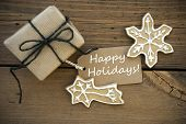 picture of ginger bread  - White Happy Holidays on a brown Banner with Ginger Bread Cookies and a Gift all on Wood - JPG