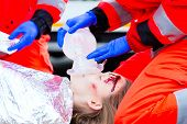 image of accident victim  - Emergency doctor and nurse or ambulance team giving oxygen to accident victim - JPG