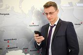 foto of ekaterinburg  - Portrait of businessman with phone leaning against wall with map - JPG