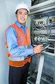picture of breaker  - Asian Indonesian Technician or electrician making function test on breaker box or switch box with power lines on construction site or in factory for acceptance - JPG