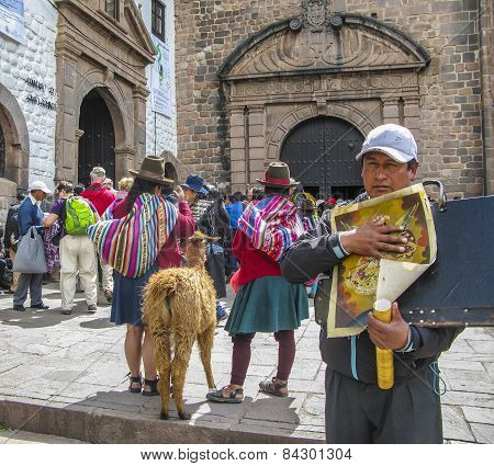 Indian Woman Pose With A Lama For Tourists In Cuzco,man Sells Paintings