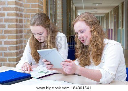 Two teenage girls studying in long school corridor