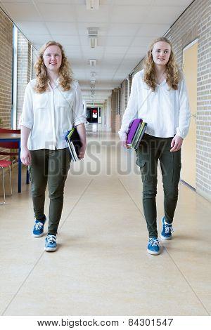 Two teenage girls walking in long school corridor
