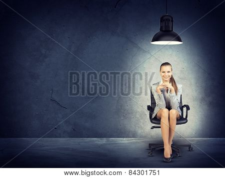 Woman wearing jacket, blouse sitting with legs crossed. Background concrete wall