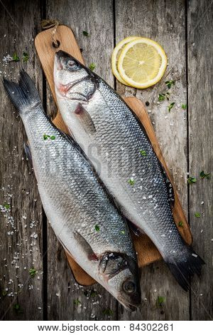 Two Raw Fresh Sea Bass On A Cutting Board With Lemon And Sea Salt
