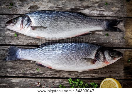 Two Raw Seabass With Fresh Thyme And Lemon On Wooden Table