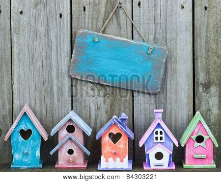 Blank wood sign hanging on fence over colorful birdhouses