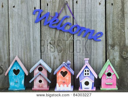 Purple welcome sign by collection of birdhouses