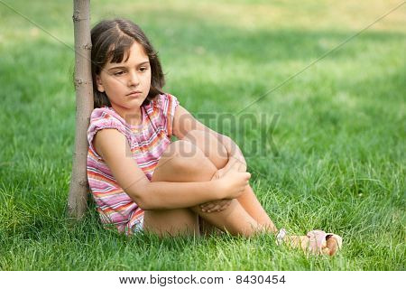 Boring Girl Sitting At The Young Tree