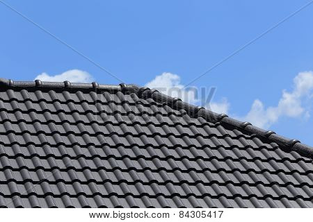 Black Tiles Roof On A New House With Blue Sky