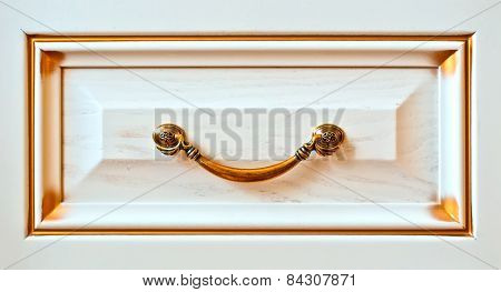 The ancient gold handle on a case door as element of design apartment interior