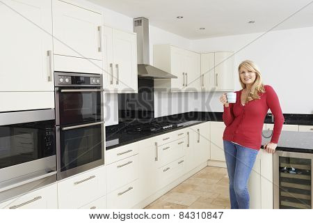 Mature Woman Standing In New Luxury Fitted Kitchen